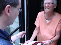 woman expressing gratitude and delight as she receives hand delivered books in her home.