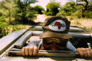 Gary Clarke peeks out from a Jeep in Africa.