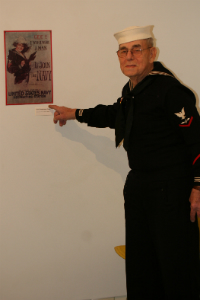 Ted Mize, in his original Navy uniform from his service in the Korea War, points to a World War 2 era recruitment sign.