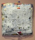 """A mixed media """"bundle"""" of layered and painted cloth"""