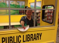 Library shelver posing with frog craft