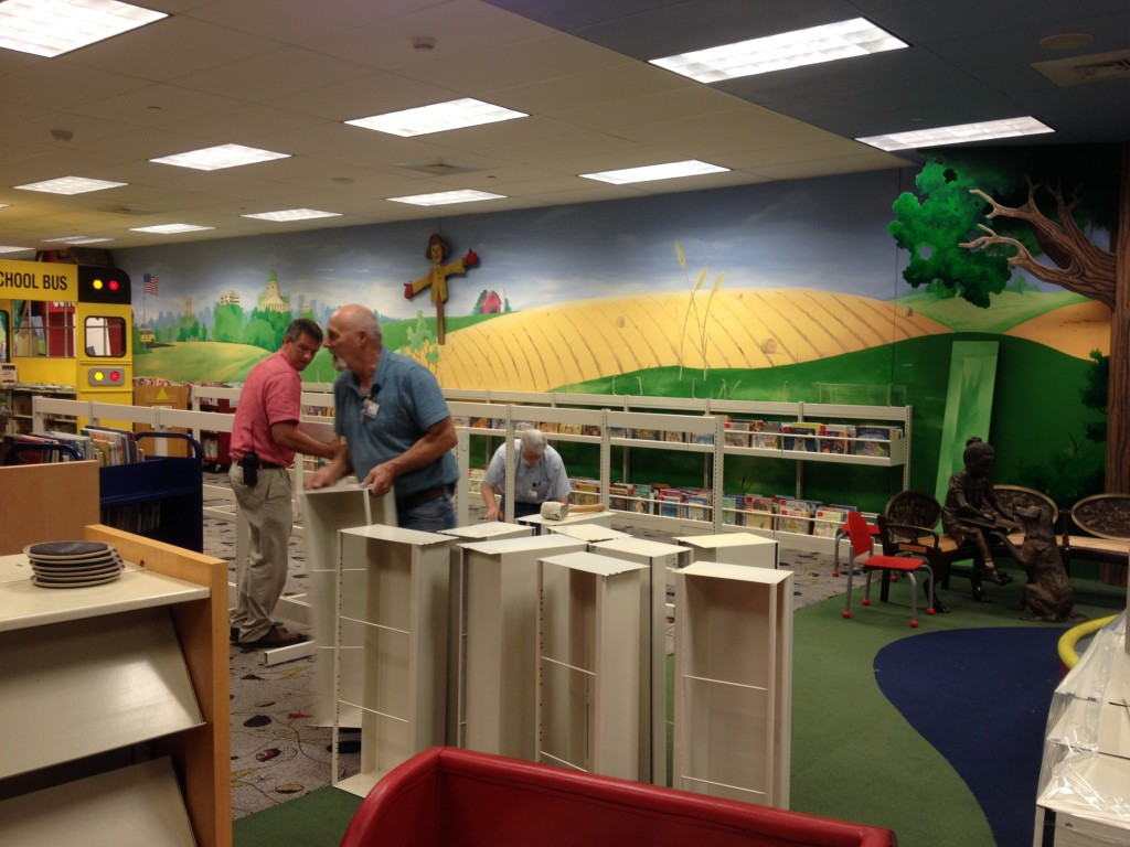 Library staff members assemble bin shelving