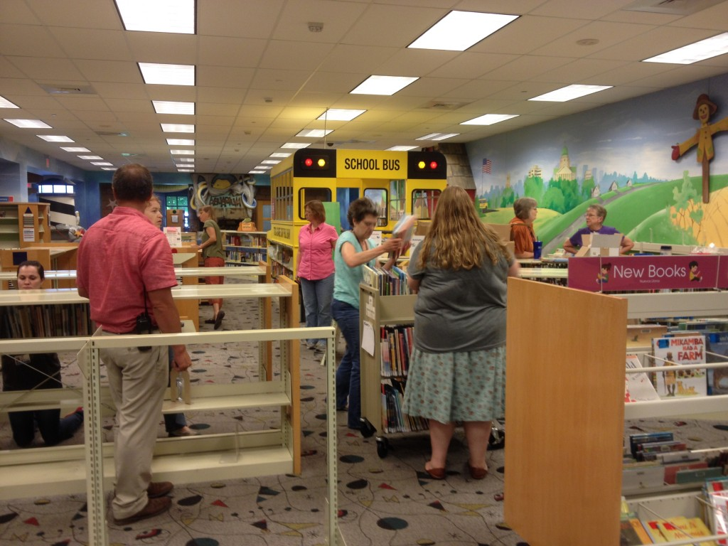 Library staff members load books onto carts