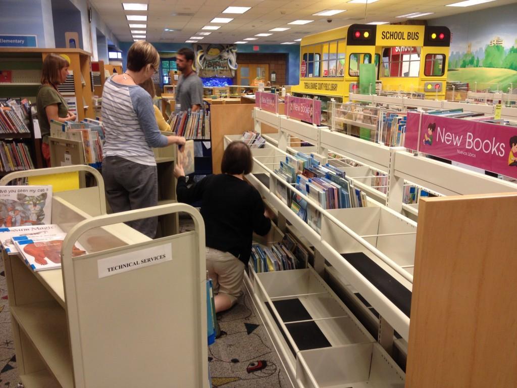 Staff members fill bin shelves