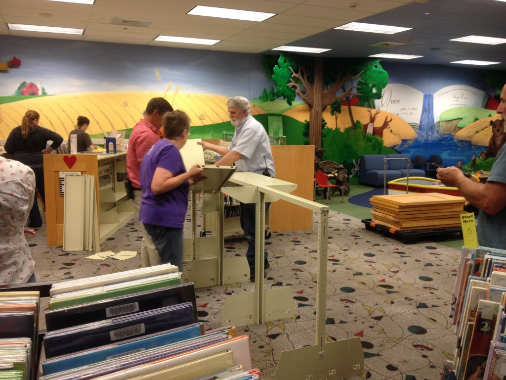 Library staff members dismantle shelves