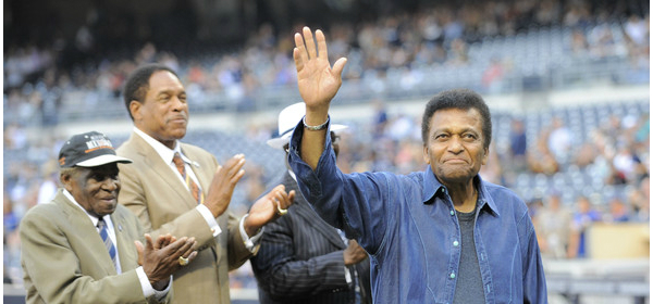 "Former Negro League player and country singer Charley Pride, right, waves to the crowd during a ""Salute to the Players of the Negro Leagues"" before a baseball game between the San Diego Padres and the Toronto Blue Jays at Petco Park on May 31, 2013 in San Diego, California."