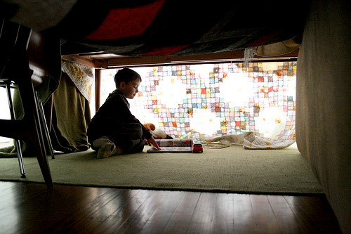 boy reading in blanket fort