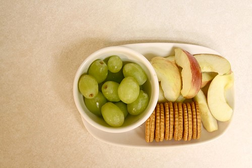 grapes, apples, and crackers arranged on a plate