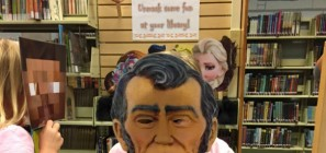 "Sign reads ""Unmask Some Fun at your Library"". Child wearing Abraham Lincoln mask."
