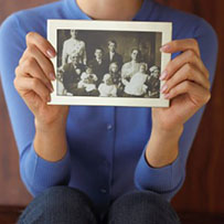 A woman holding a black and white photograph of her ancestors.