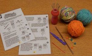 Spool-knitting kit includes instructions, yarn, spool, beads, and other tools.