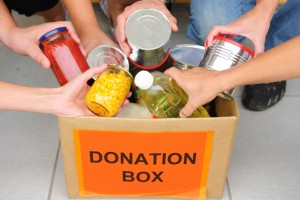 people donating canned goods to a donation box