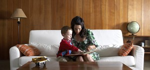 Mother and son (3-5) on couch, reading in living room