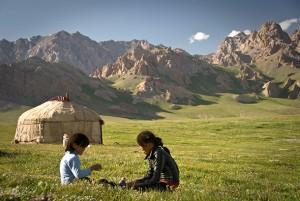 BGD57H Kyrgyz Children playing on the grass, Irkestan Pass, Kyrgyzstan