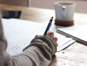 Close up of a hand writing with a pen on papers on a desk. A mug rests on the table in the background.