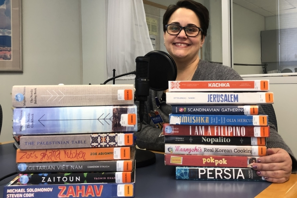 Michelle Stottlemire poses with some of the many stacks of international cookbooks she brought to the podcast recording studio!