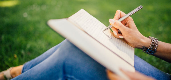 Close up image of person, sitting outside, writing in journal
