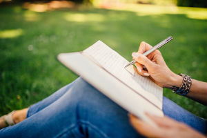 Close up image of person writing in a notebook with grass in the background