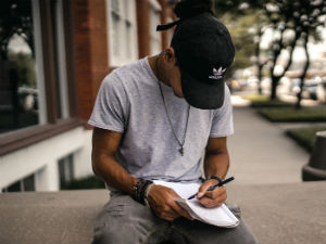 Man writing in notebook while sitting on a concrete ledge outside