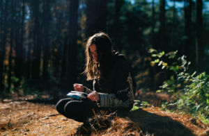 Woman crouched in a forest setting with notebook and pen in hand