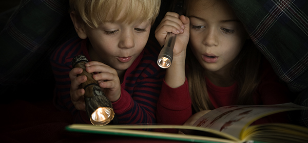 Children Reading Book by Flashlight Under Covers