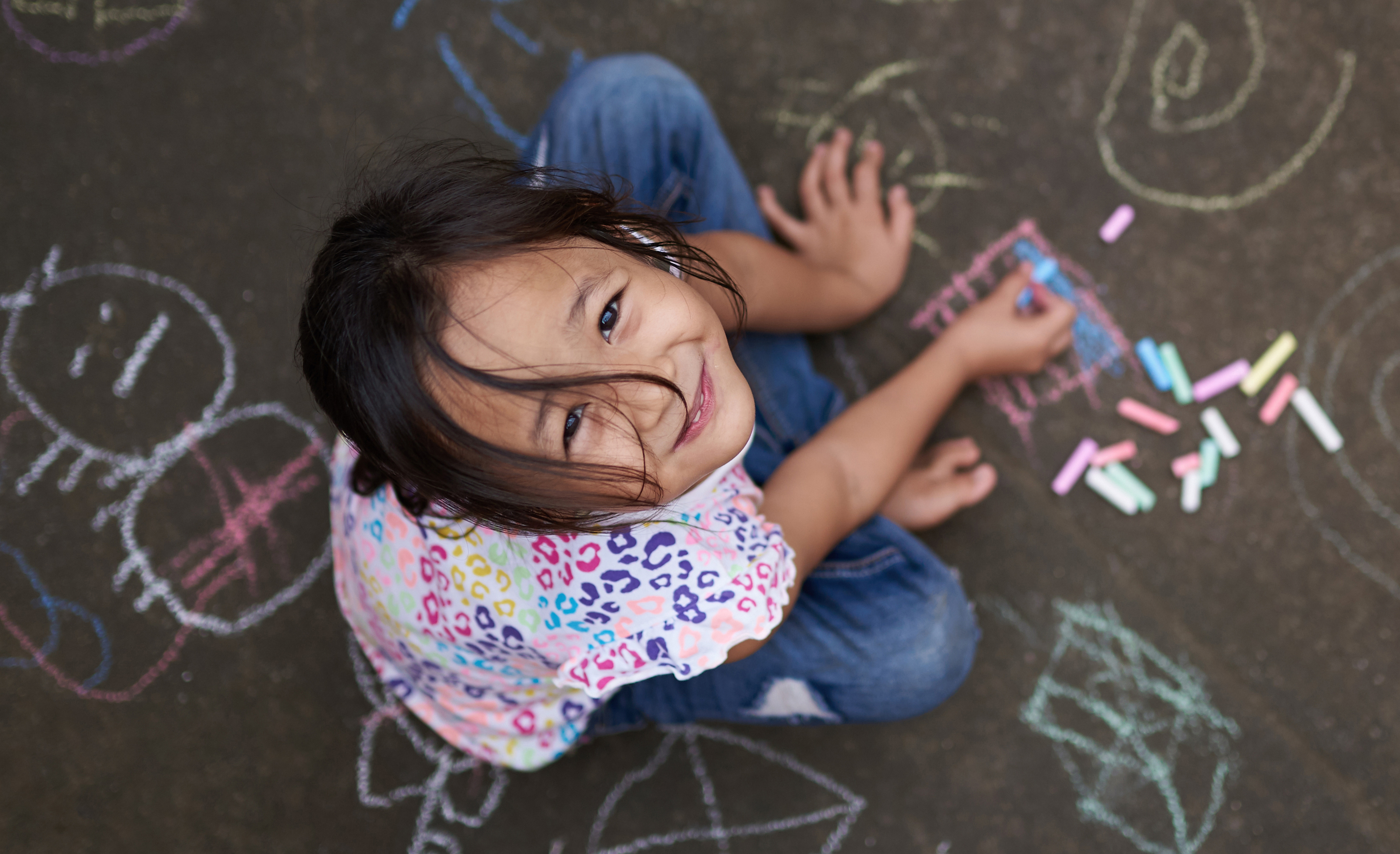 small girl with chalk on painted asphalt background above top view