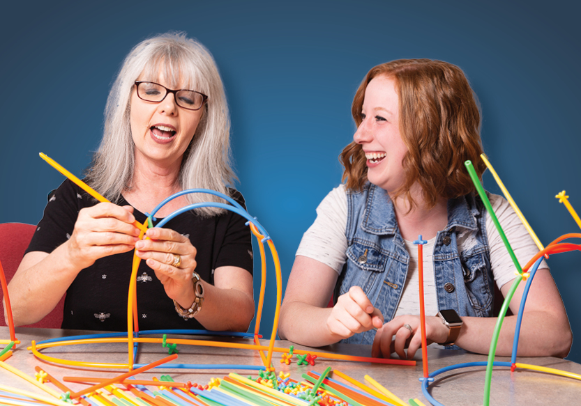 2 ladies building with colorful straws