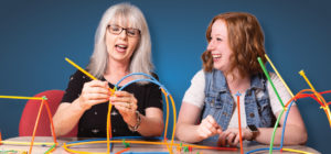 two ladies building with colorful straws