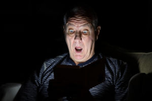 Man in a dark room, reading a scary story on his tablet.