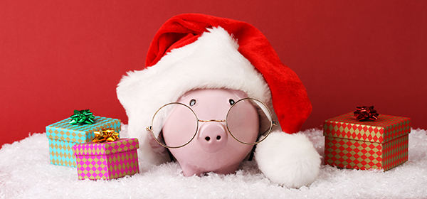 Piggy bank with presents and Santa hat