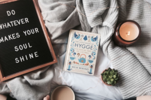 "The Little Book of Hygge is surrounded by comfy blankets, a lit candle, succulents, and a sign that says, ""Do whatever makes your soul shine."" A person holds a cup of cocoa in the bottom of the frame."