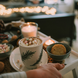 A person is holding a tray containing a lit candle, a cup of hot cocoa with mutli-colored marshmallows, and a cookie. There are twinkle lights blurred in the background.