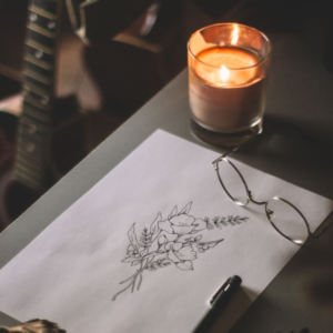 A table with a drawing of flowers, a pen, glasses, and a lit candle on it. There is a guitar in the background.