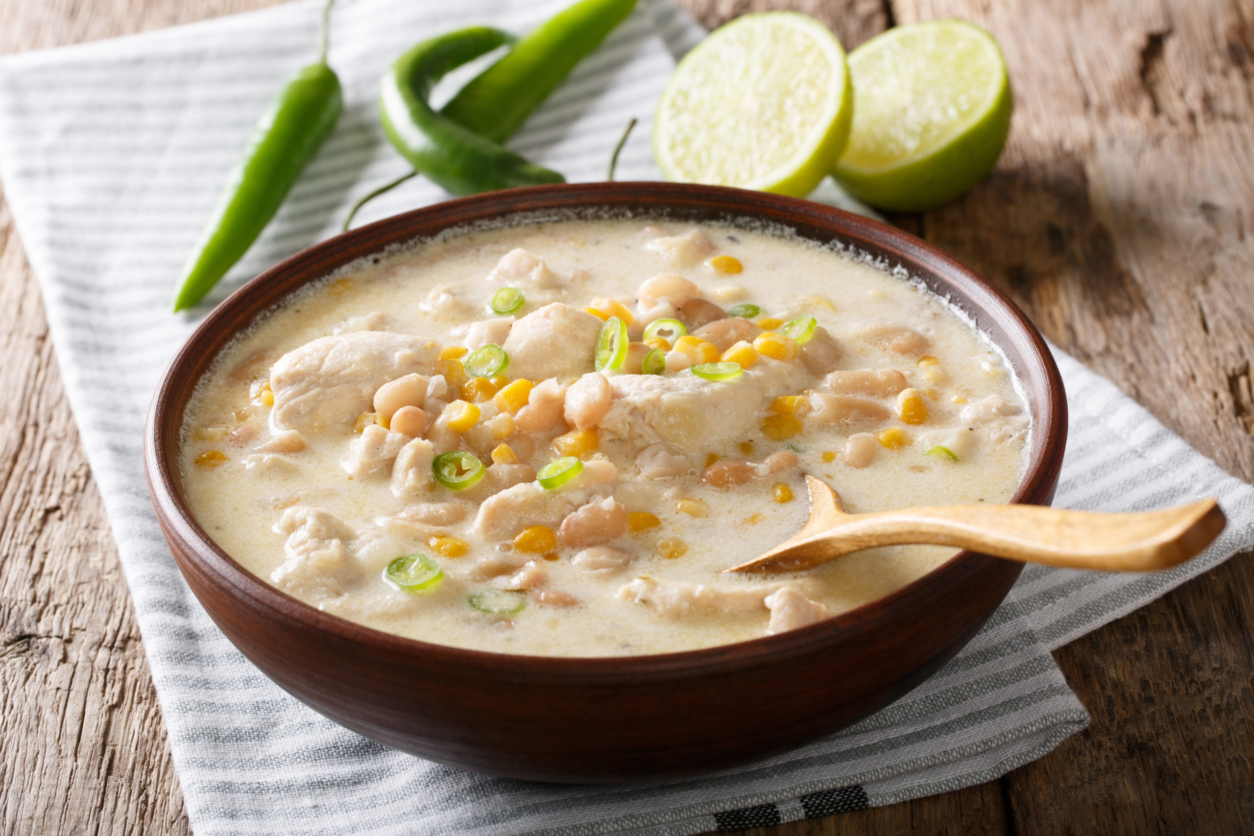 Homemade white chili chicken with beans, lime and corn close-up on the table