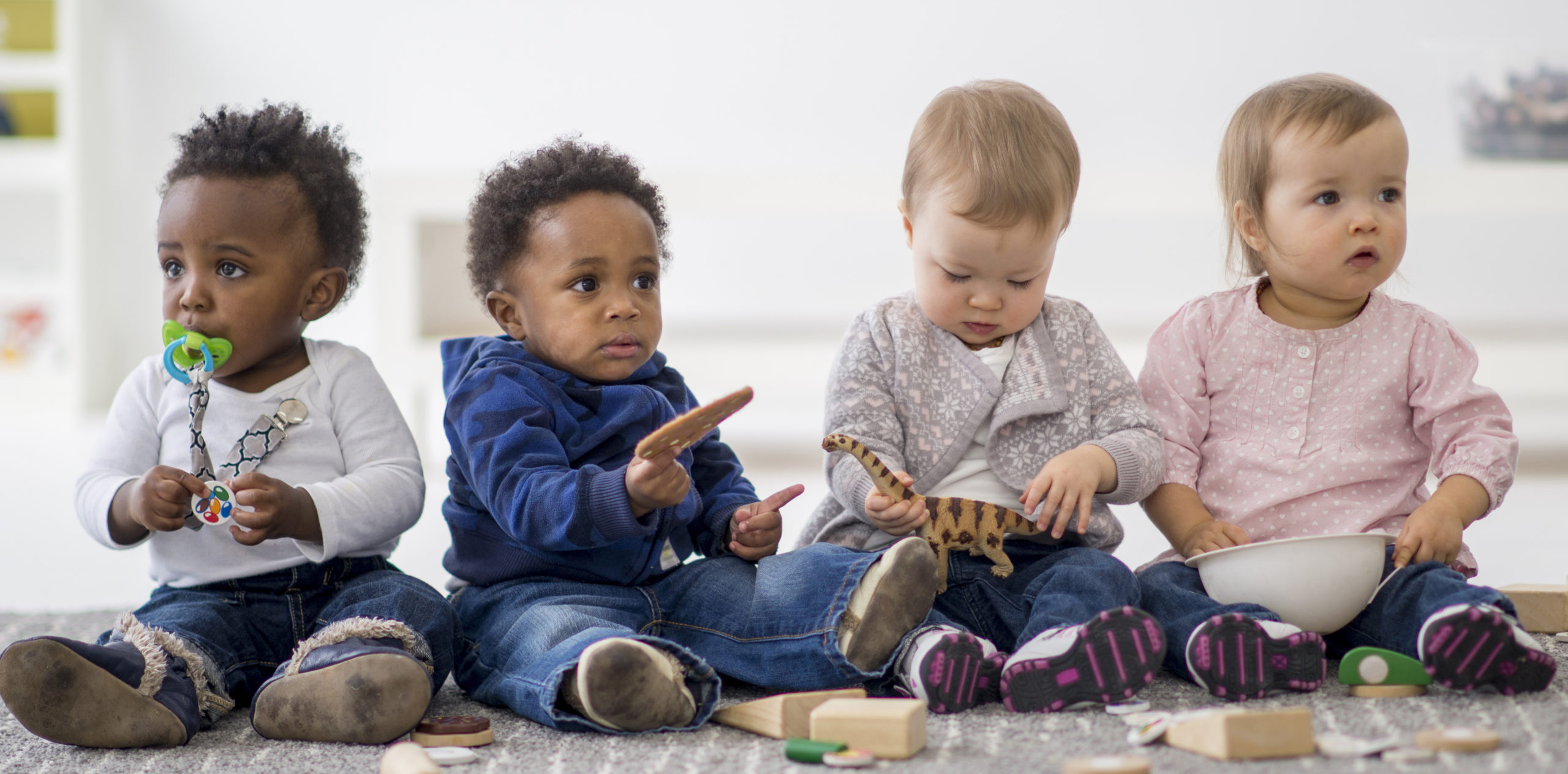 group of toddlers playing together with toys