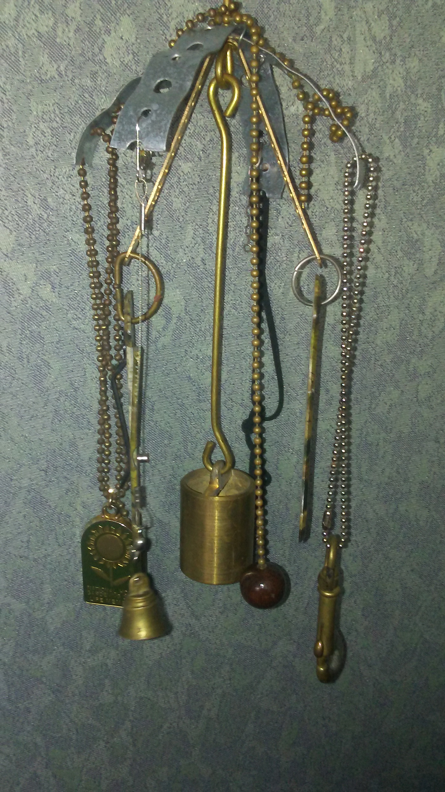 Metal Wind Chime Made of Found Objects Including Brass weight, Clamps, Lamp chain, Green and Brass Key fob, Brass Bell, Green Camo Pocket Knife Parts.