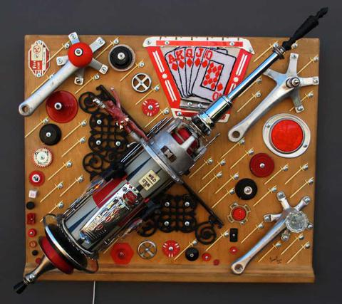 Sculpture of rocket using hardware and machine parts along with black, red and white plastic and graphic elements.