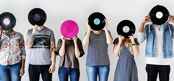 People holding records in front of faces