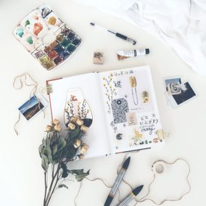 An open journal full of doodles and positive messages. It is surrounded by art supplies and flowers