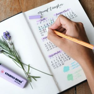 A woman's hand is updating a decorated bullet journal calendar with a pencil. Some lavender and a purple highlighter rest upon the opposite page.
