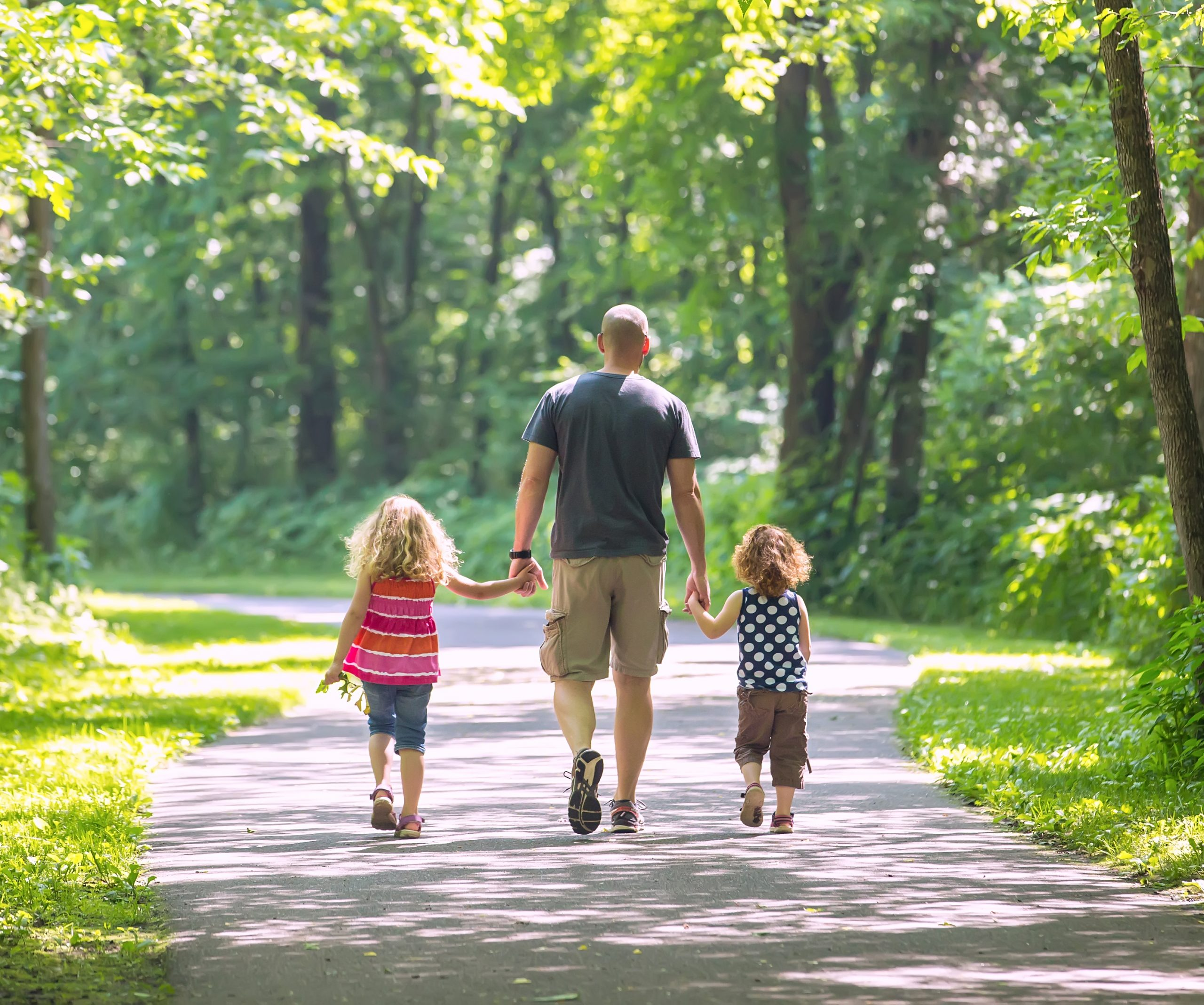 a father and his two young daughters going for a walk on a paved trail through the wooded park.