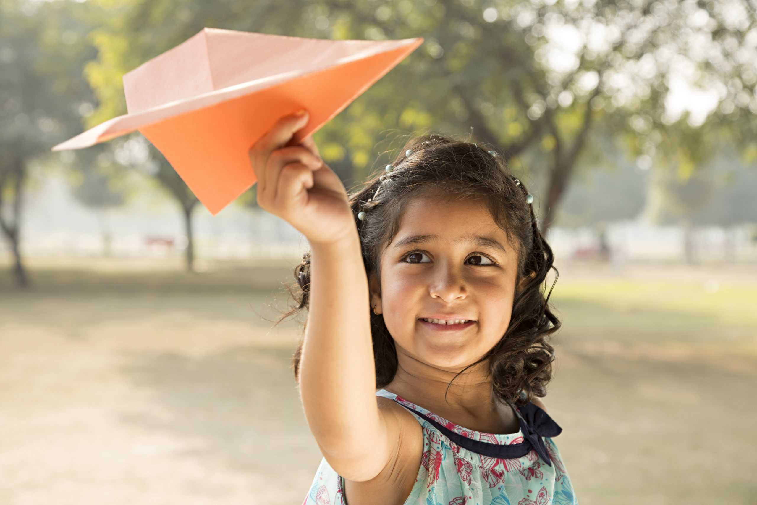 Girl playing with paper airplane