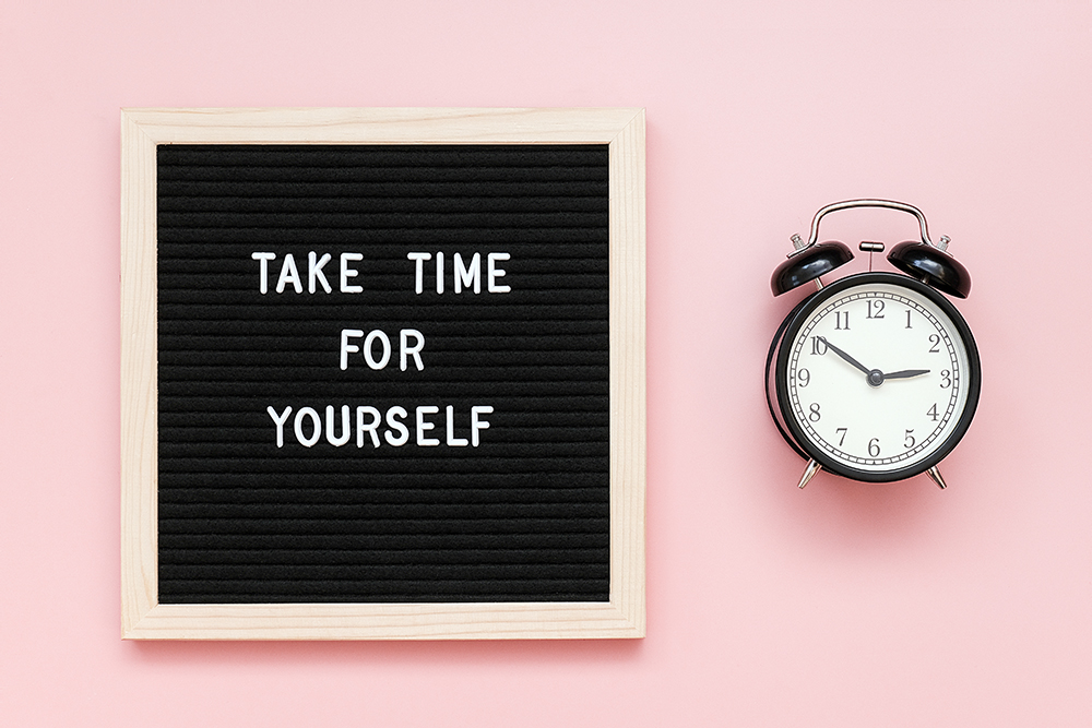 Take time for yourself. Motivational quote on letterboard and black alarm clock on pink background.