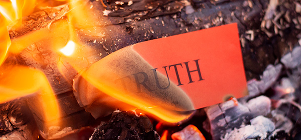 Red paper with inscription TRUTH burning in fire