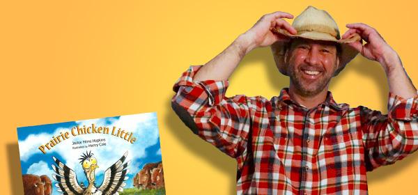 Kyler in a cowboy hat with the book Prairie Chicken Little