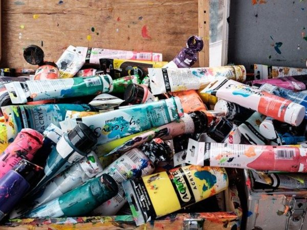 A pile of various colors of acrylic paints in tubes on a messy art desk