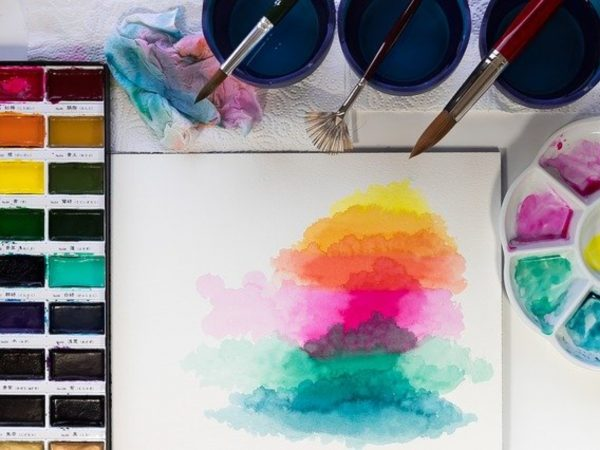 A white surface with a pan of watercolor paints, some vessels with colored water and paintbrushes, a palette with magenta, teal, and blue paints surrounding a piece of watercolor paper with layers of yellow, magenta and teal shapes painted upon it