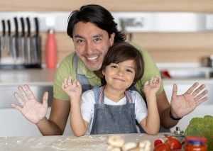 father and son having fun making homemade bread and smiling with flour on their hands and faces