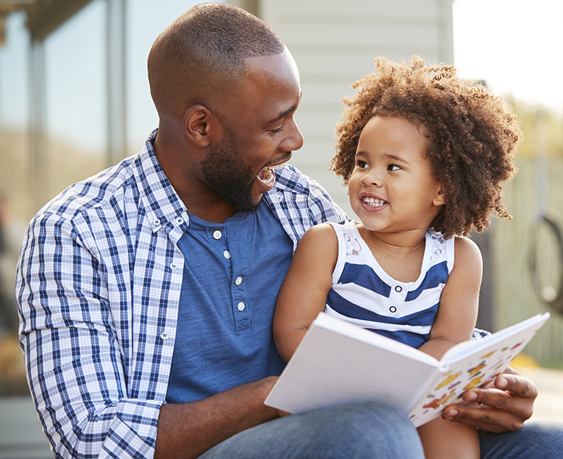 father and daughter reading book outside