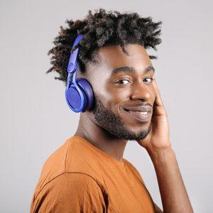 Man wearing an orange t-shirt and blue headphones